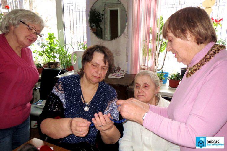 Бабушки обсуждают и примеряют изделия из бисера